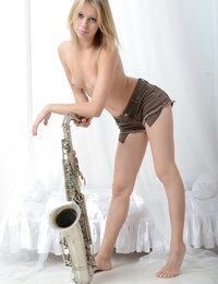 Adorable shapely beauty with a tattoo on her right arm posing in the nude with saxophone.