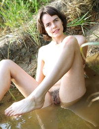 Rimma looks content and happy playing in the lake nude with orange jug