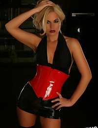 Blonde Alluring Vixen babe Charlie teases in her red vinyl corset as she gets topless
