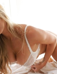 Gisele posing naked between white sheets